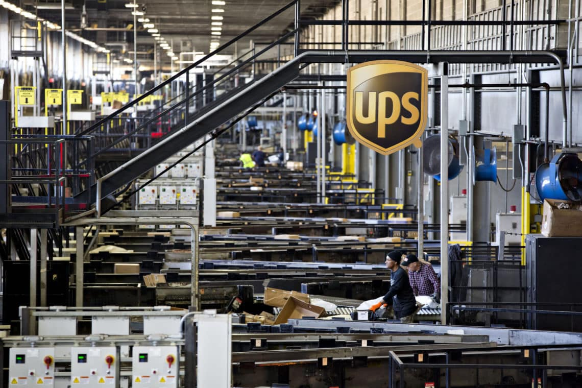 A logo hangs above conveyors moving packages arriving at the United Parcel Service Inc. (UPS) Chicago Area Consolidation Hub in Hodgkins, Illinois, U.S., on Tuesday, Dec. 5, 2017. Photographer: Daniel Acker/Bloomberg